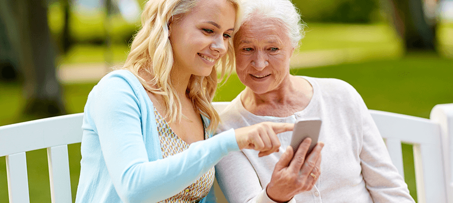 woman helping older woman use resident portal on smartphone