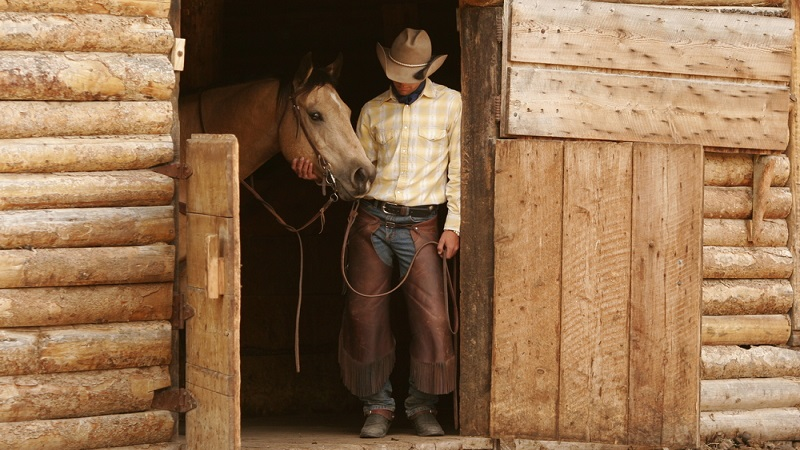 A cowboy with horse by door of stable