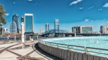 A shot of city buildings near a large, man-made fountain on a sunny day in Jacksonville, FL.