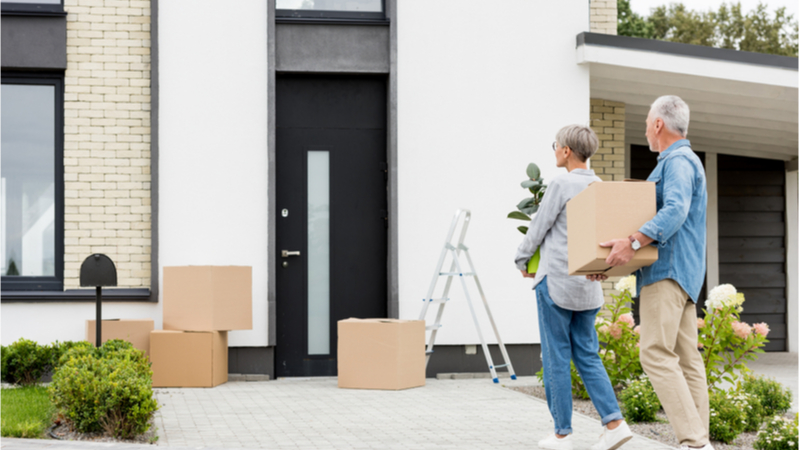 Couple with storage boxes outside home