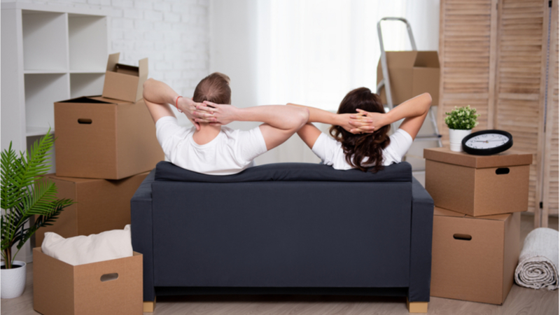 Young Couple on Sofa Surrounded by Packing Boxes