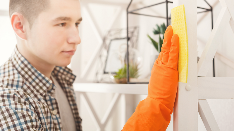 man cleaning shelf in apartment