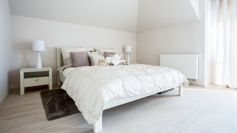 A simple bedroom with a white matching furniture set consisting of a bed and two bedside tables.
